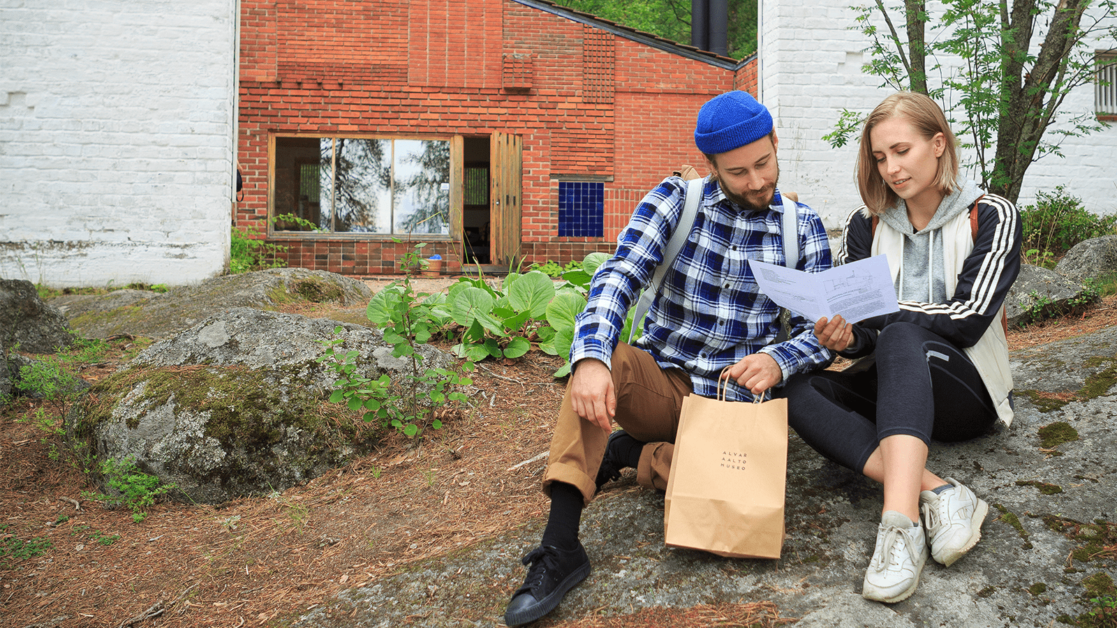 Two persons sitting on a rock and reading in front of Muuratsalo Experimental House.