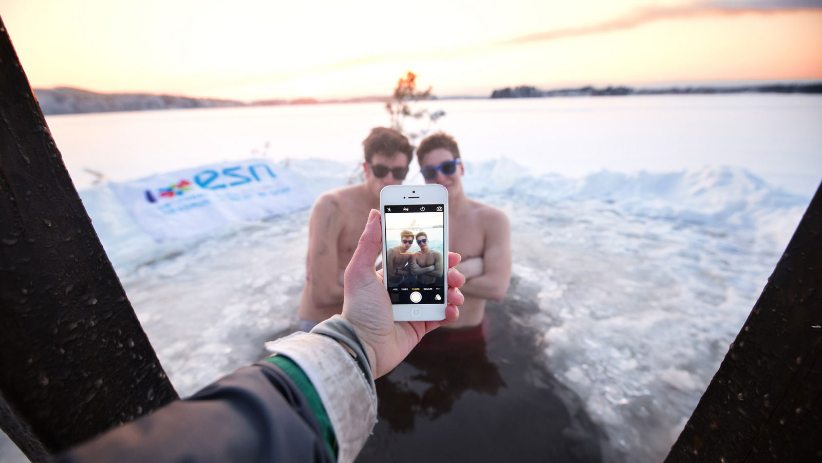 Two persons are being photographed in ice hole in winter.