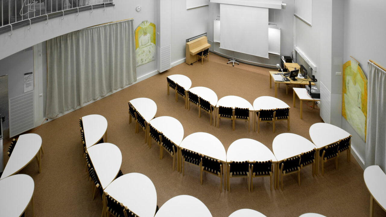 Auditorium with tables and chairs.
