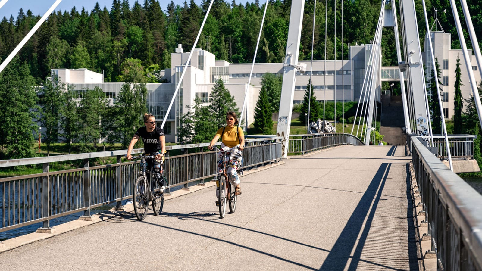 Two persons cycling on the bridge.