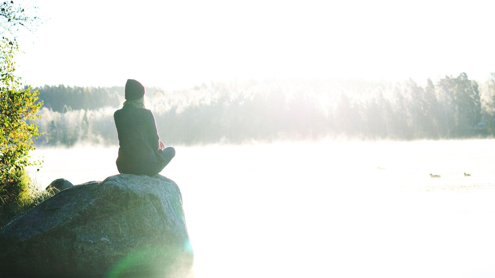 Henkilö istuu kivellä luontomaiseman äärellä