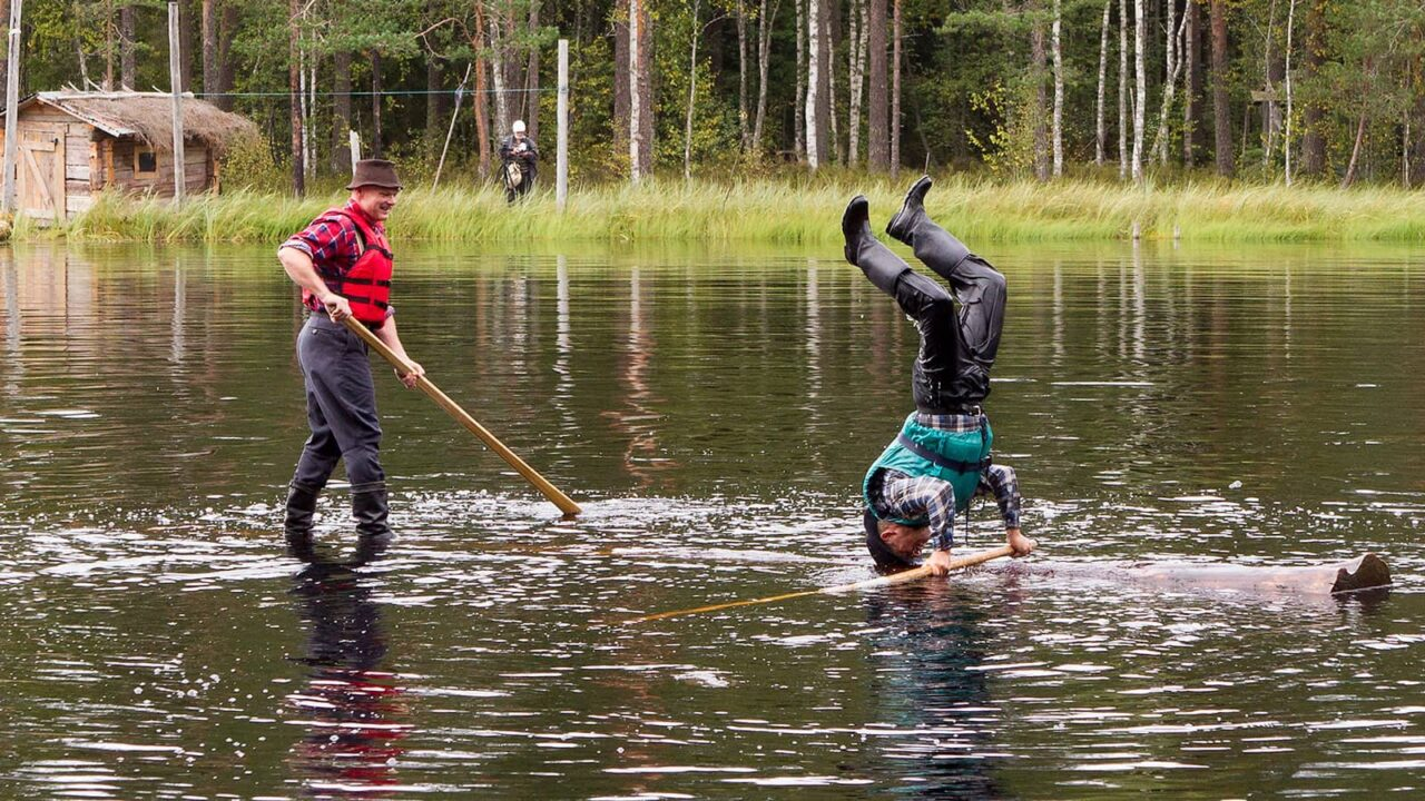 One person standing and other person standing on his head on a log in the water