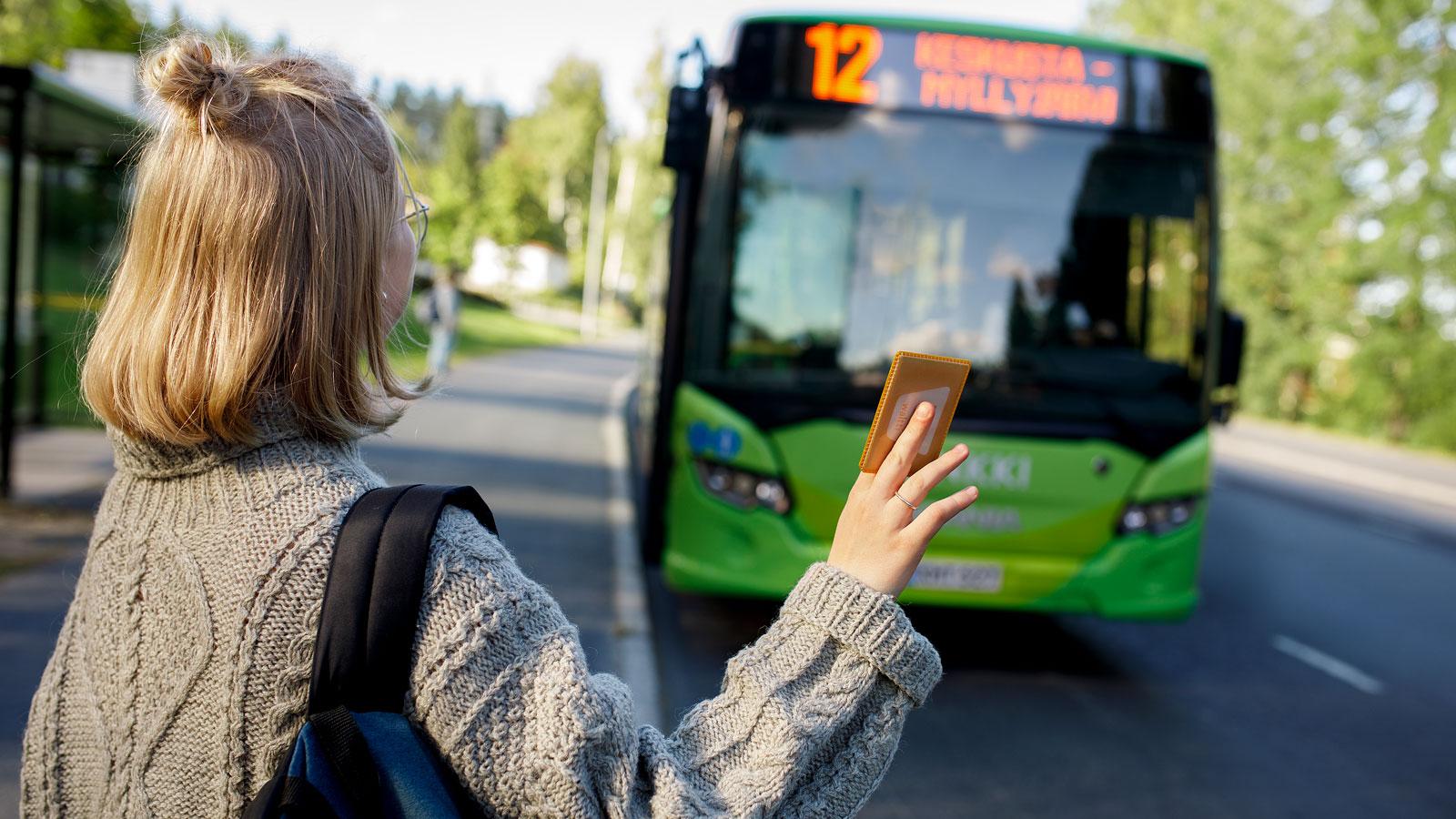 Henkilö viittomassa bussia bussipysäkille.