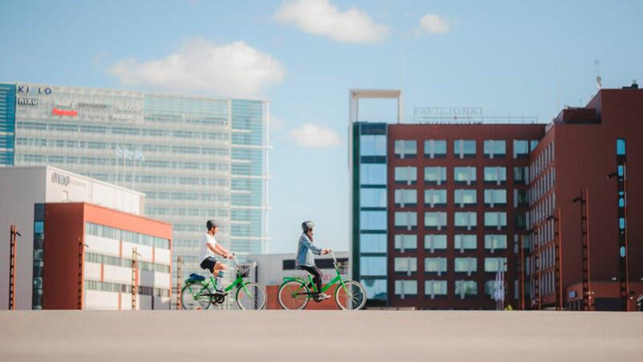 Henkilöt pyöräilemässä Solo Sokos Hotel Paviljongin rakennuksen edessä.