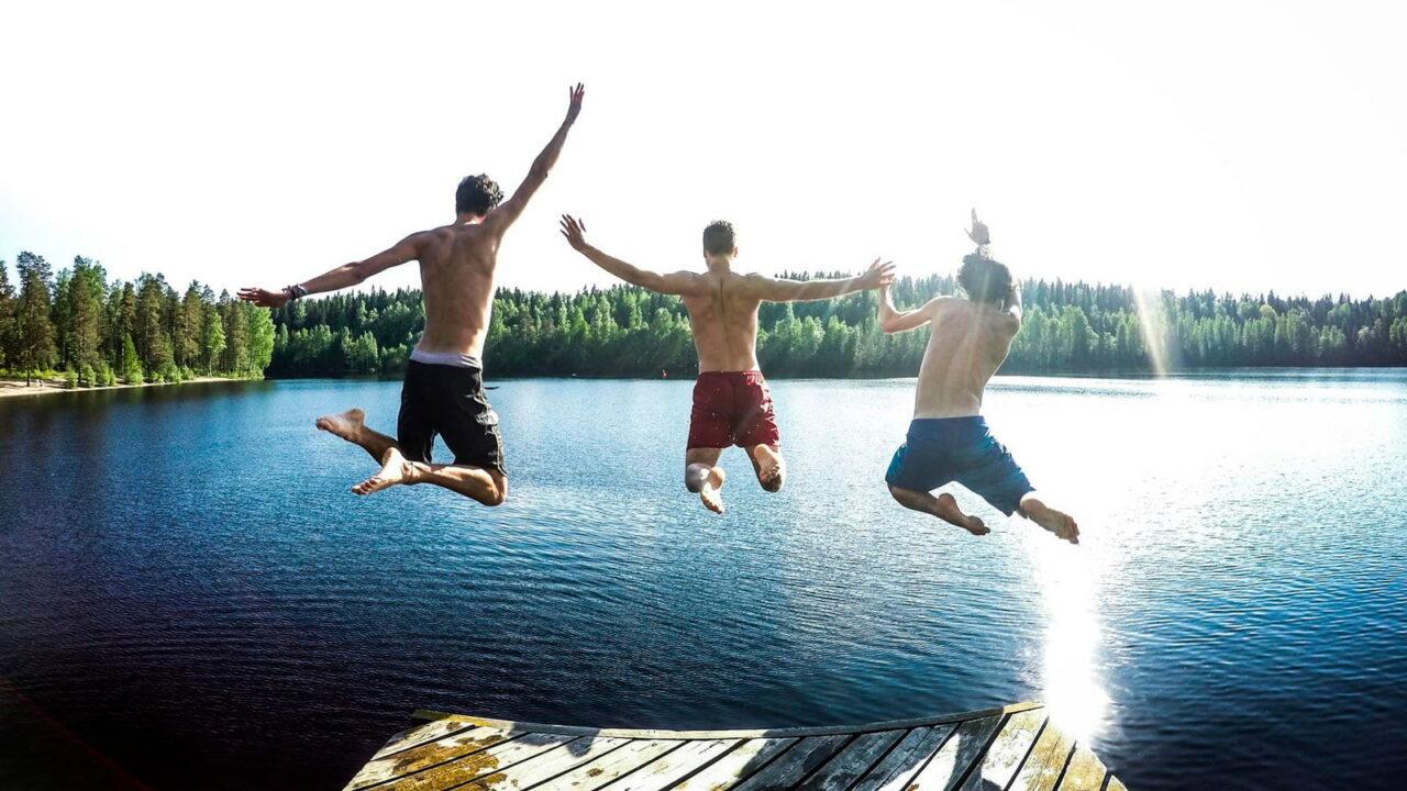 Kolme henkilöä hyppäämässä laiturilta järveen.