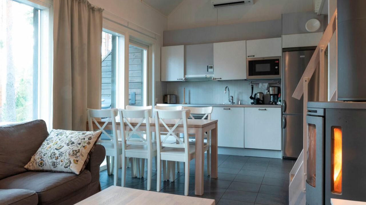 Varjolan Riihisuite, jossa on keittiö, ruokailuryhmä, sohva ja takka.