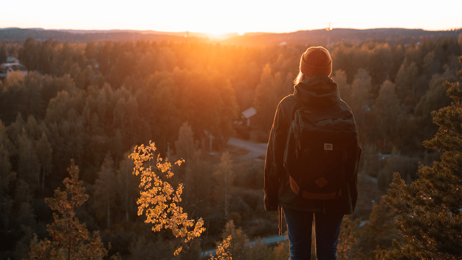 Henkilö katsoo auringonlaskua.