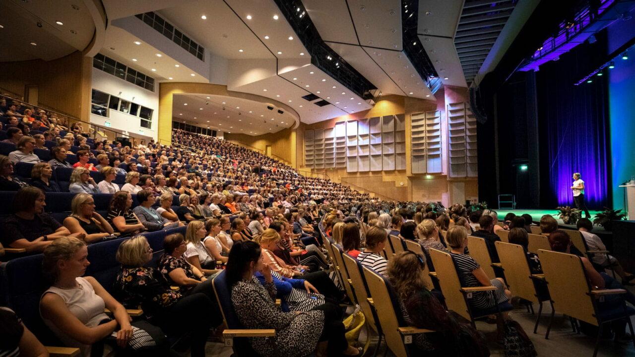 Henkilöitä istumassa kongressisalissa.