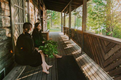 Kaksi henkilöä istuu saunarakennuksen terassilla.