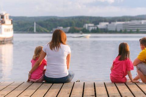 Kaksi aikuista ja kaksi lasta istuu laiturilla Jyväskylän Lutakon satamassa.