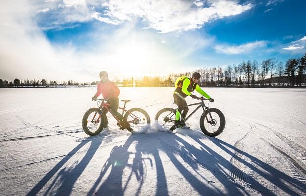 Kaksi henkilöä ajaa fatbike- pyörillä