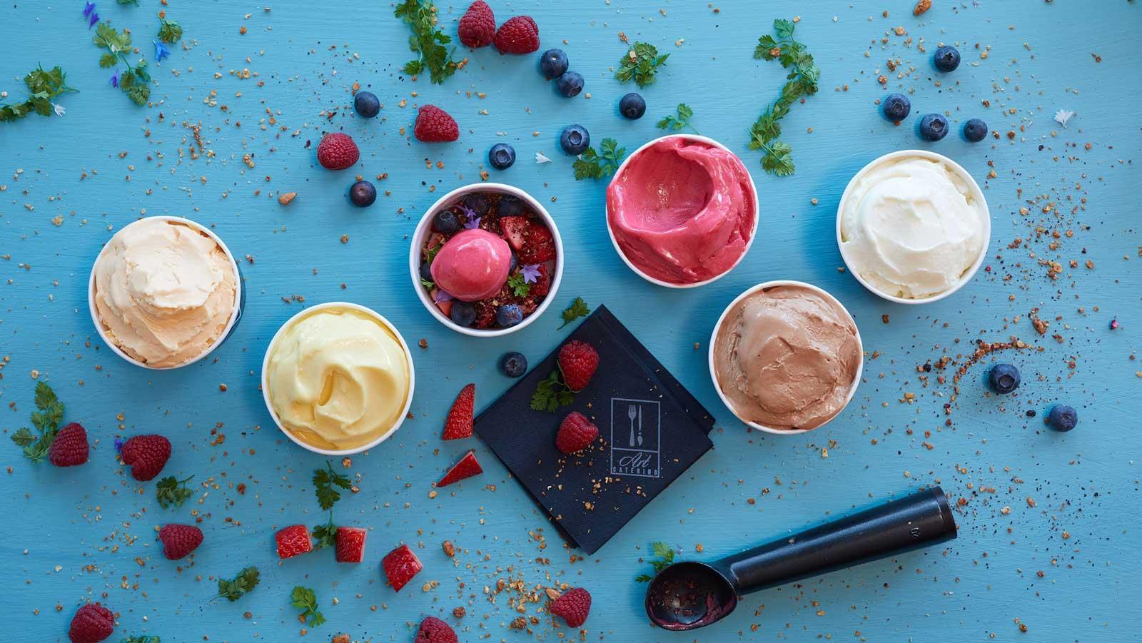 Jäätelöä ja marjoja pienissä kipoissa pöydällä sekä jäätelökauha