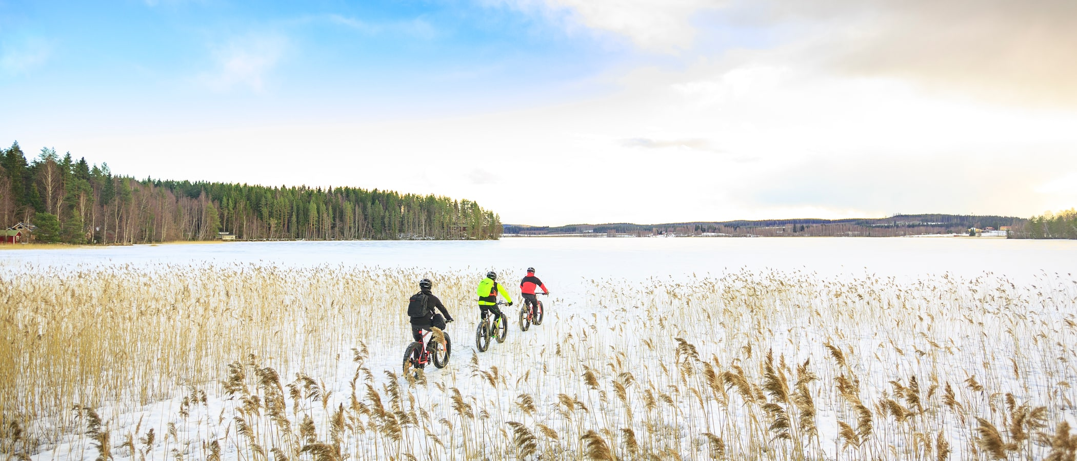 Three people riding their fatbikes on the lake ice