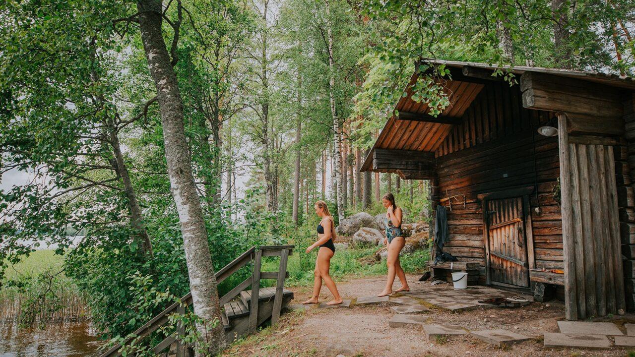 Zwei Personen gehen nach einer Rauchsauna Schwimmen in der Region Jyväskylä, Sauna-Region.