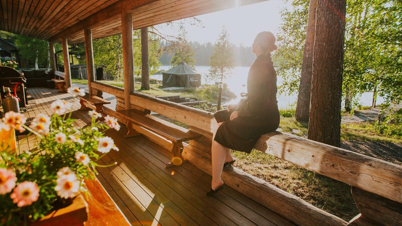 Henkilö istuu saunan terassilla auringonpaisteessa