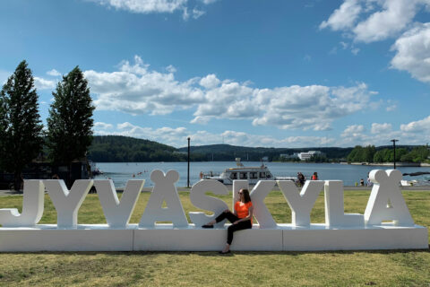 A person sitting on a bench made of letters forming the word Jyväskylä in Lutakko harbour