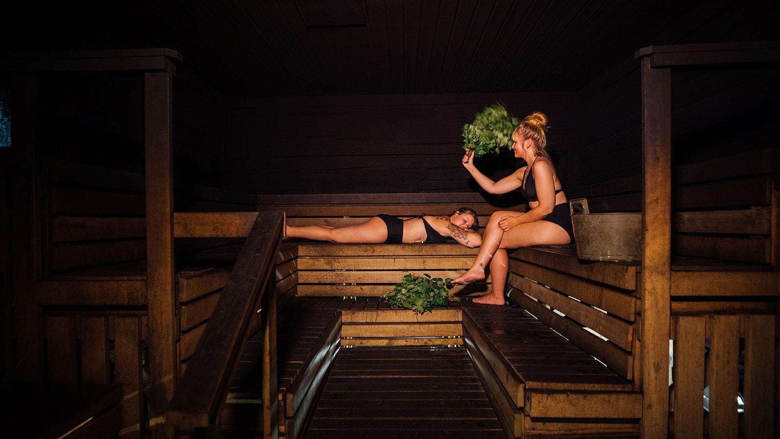Kaksi henkilöä istuu savusaunassa ja käyttävät saunavastaa