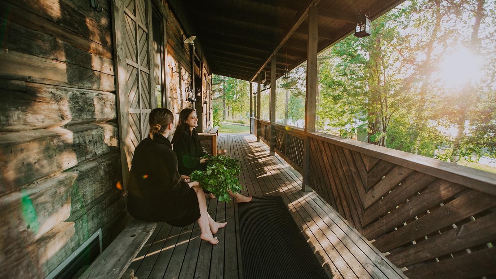 Kaksi henkilöä istumassa savusaunan terassilla