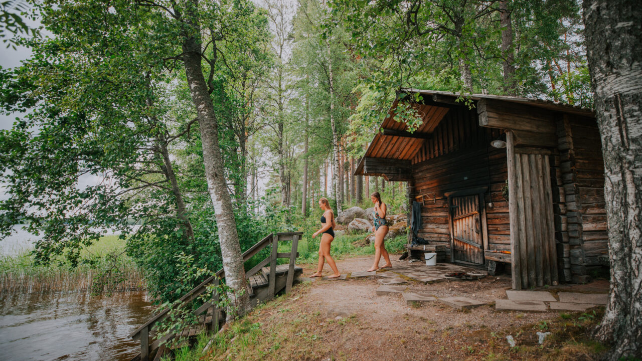 Two persons walking from the sauna in order to have a swim in the lake