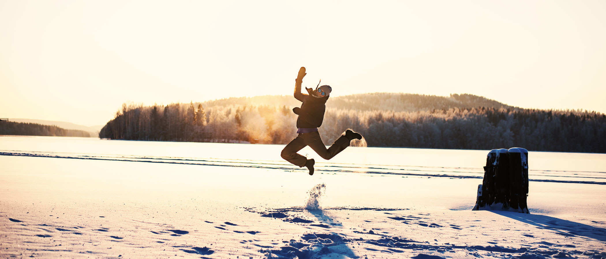 A person jumping in the air in winter
