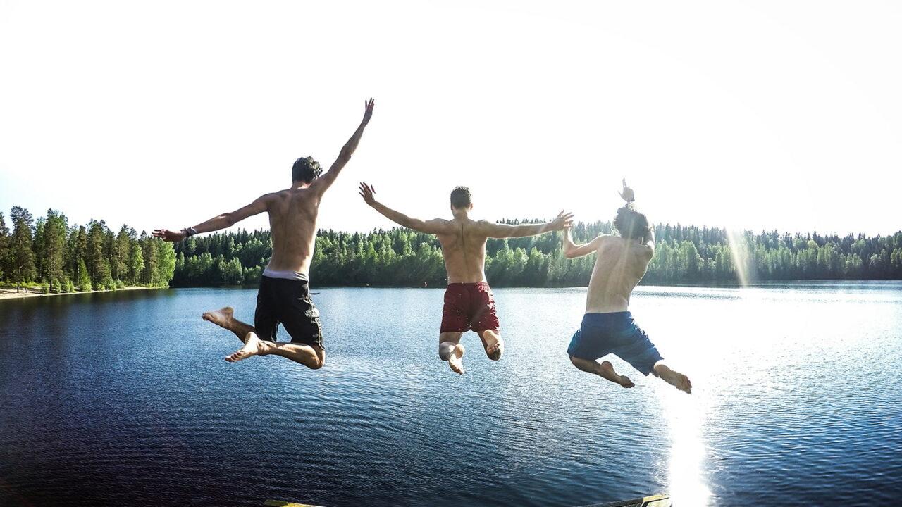 Kolme ihmistä hyppää uimaan järveen