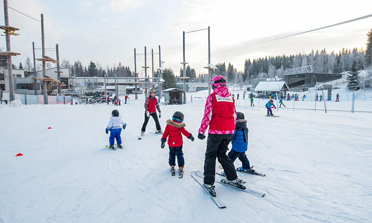Hiihdonopettaja opettaa lapsia Laajiksen hiihtokeskuksessa laskettelemaan,