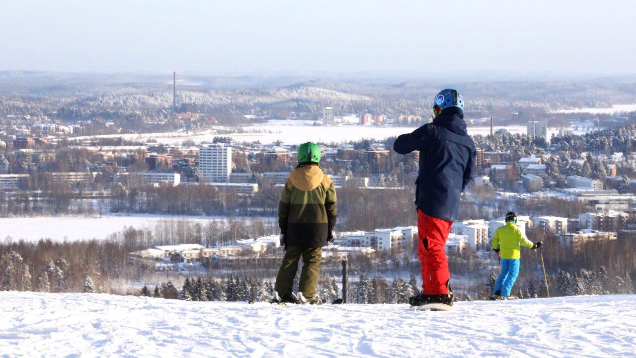 Människor åker slalom på en bergstopp på vintern.