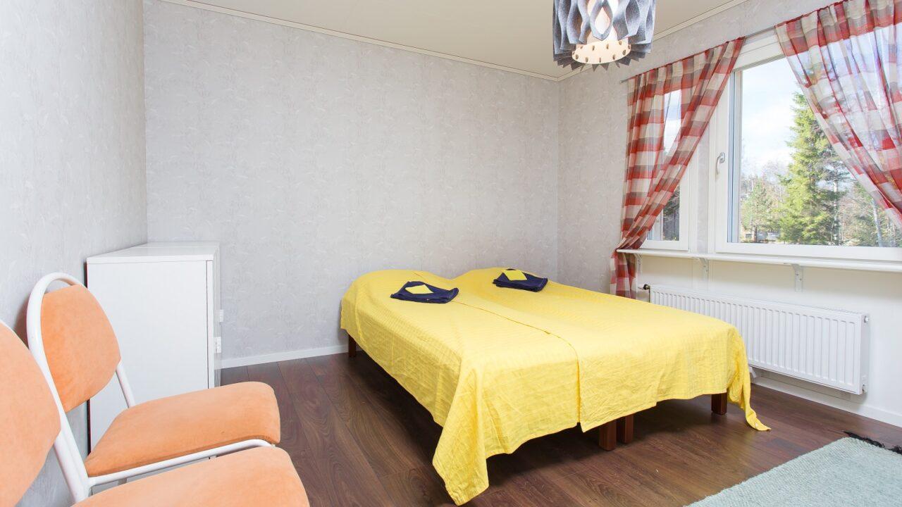 Huonekuva jossa sänky keltaisella peitolla.
