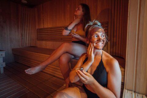 Kaksi naista saunassa tekemässä kasvonaamioita.