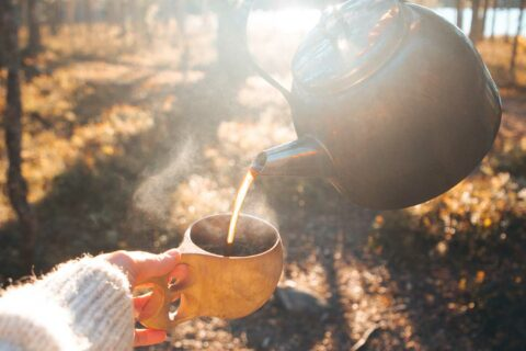 A person pours coffee from a coffee pot to a wooden cup.