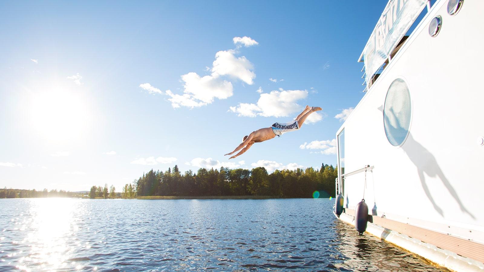 Henkilö hyppää järveen Houseboatilta