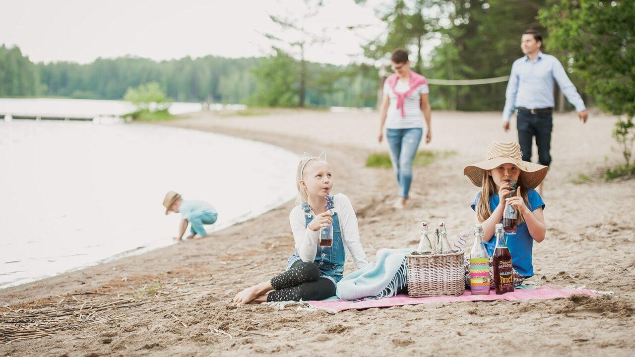 Kolme lasta ja kaksi aikuista oleilee rannalla Piispalassa