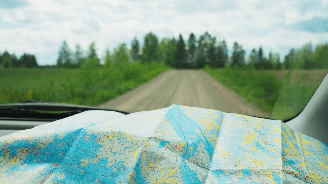 A map on the front and on the background a view of a Finnish dirt road through a windshield