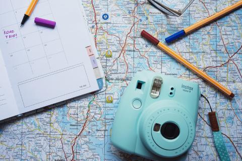 Asetelma kartasta, kamerasta, kynistä ja kalenterista