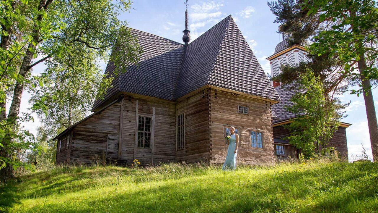 Ihminen seisoo Petäjäveden vanhan kirkon edessä