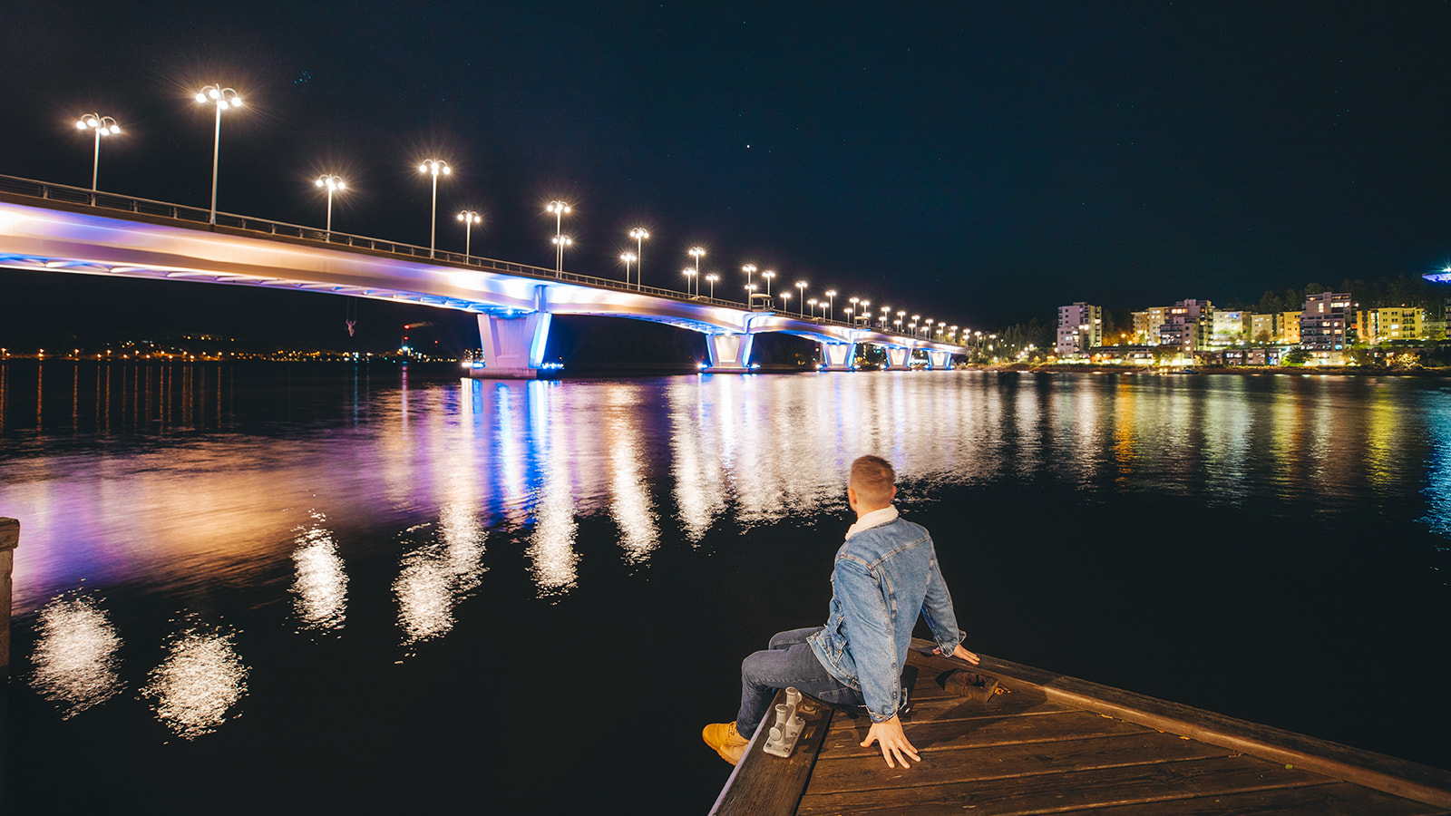 Henkilö istuu laiturilla ja katsoo valaistun Kuokkalan sillan suuntaan.