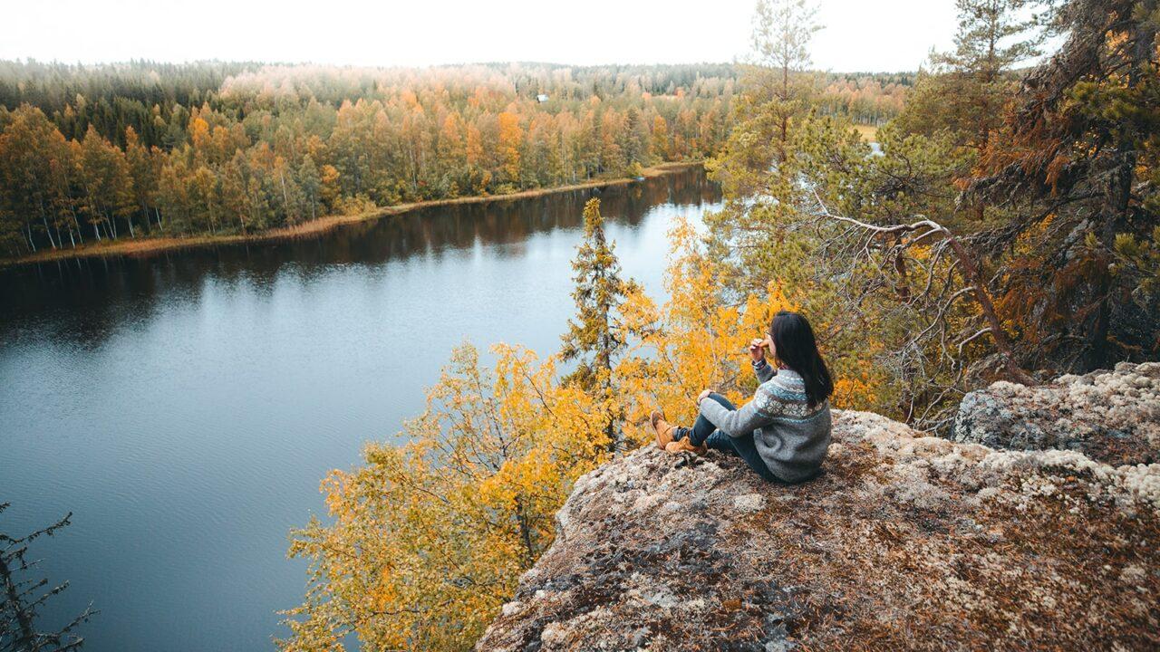 Henkilö istuu kalliolla katsomassa maisemia Lomaseudulla