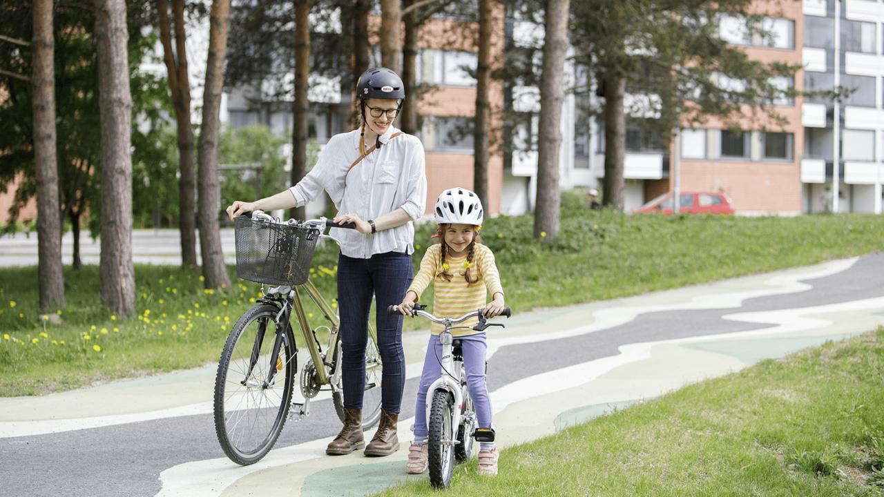 Aikuinen taluttaa pyöräänsä ja lapsi pyöräilee