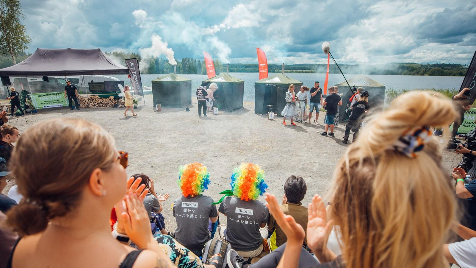 Zwei Personen lächeln in die Menge anlässlich der Weltmeisterschaften im Saunaeinheizen bei Peurunka in der Region Jyväskylä.
