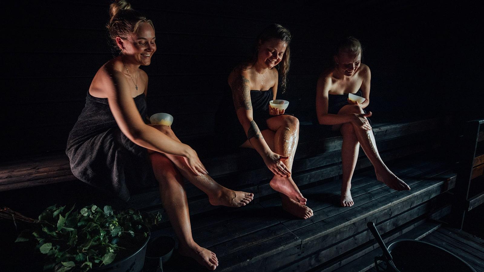 Drei Personen beim Saunabaden in der Rauchsauna von Varjola.