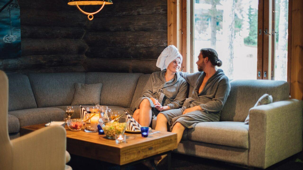 Kaksi henkilöä istuvat ja rentoutuvat saunan jälkeen pyyhkeet päällä