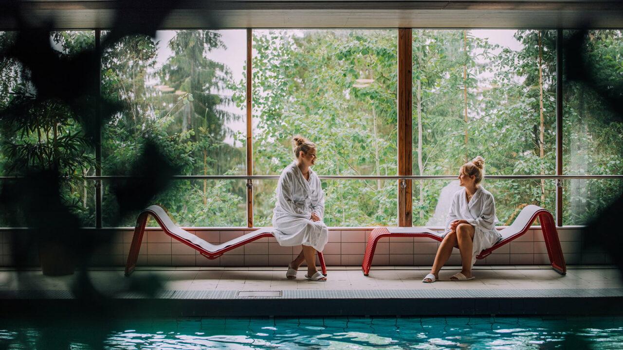 Kaksi ihmistä istuu lepotuoleilla kylpyläaltaan vieressä.