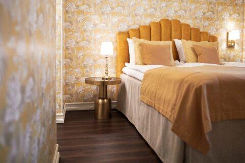 Keltaisilla tekstiileillä koristeltu sänky hotellihuoneessa