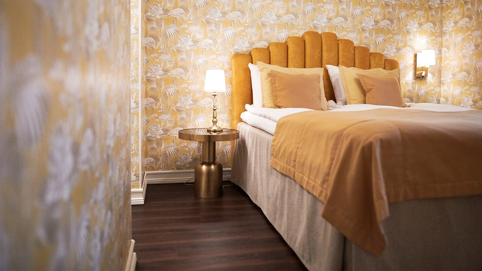 Bed decorated with yellow textiles in a hotel room