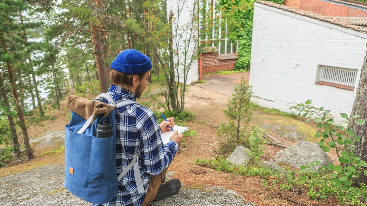 Henkilö kirjoittamassa kalliolla Muuratsalon koetalon vieressä