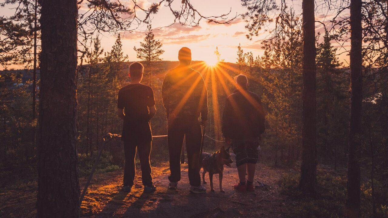 Kolme ihmistä ja koira katsoo auringonlaskua Kanavuorella Jyväskylässä.