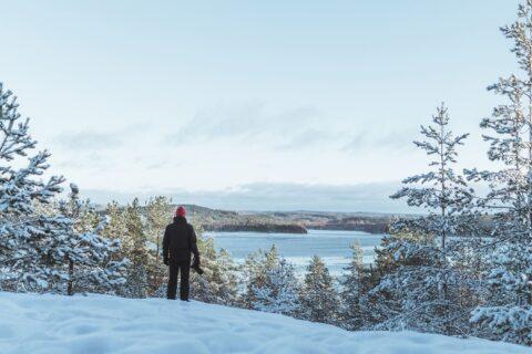 Ihminen seisoo Paljaspää-nimisen kallion päällä, taustalla järvimaisema.