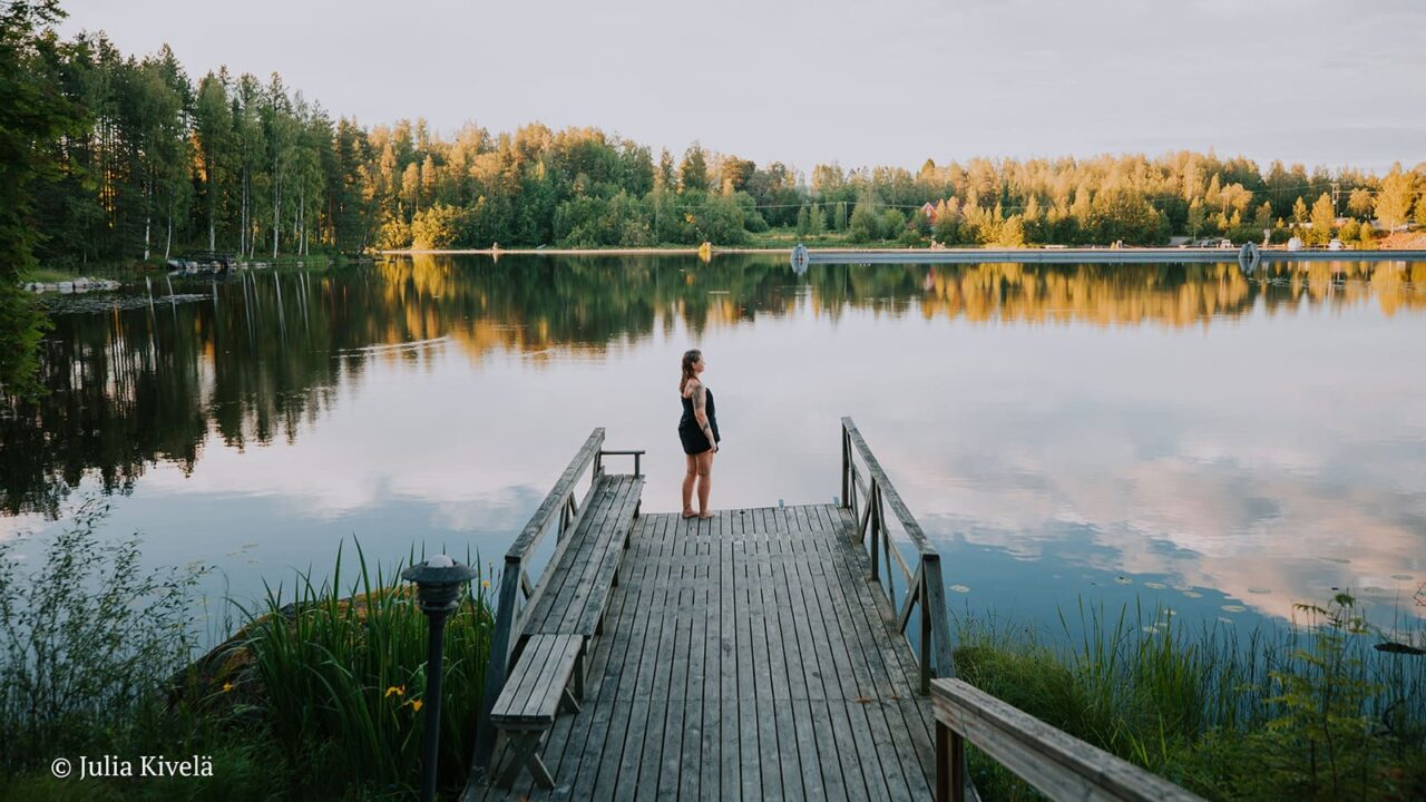 A person is standing on Varjola Resort's pier and watching the views