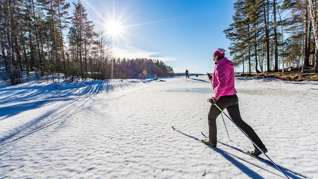 Henkilö hiihtää aurinkoisessa talvimaisemassa.