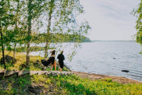 Kaksi henkilöä kulkee portaita pitkin kohti järveä.